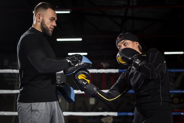 リングで練習する女性のボクサーの側面図