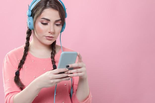 ヘッドフォンを着用しながら彼女の電話を見ている女性の正面図
