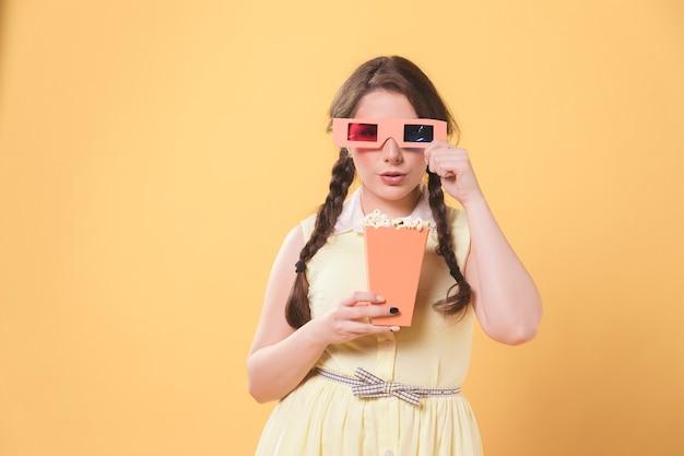 映画のメガネを着用し、ポップコーンを保持している女性の正面図