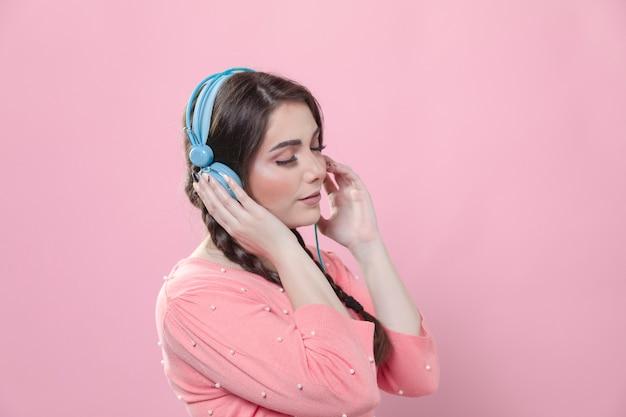 ヘッドフォンで音楽を楽しむ女性の側面図