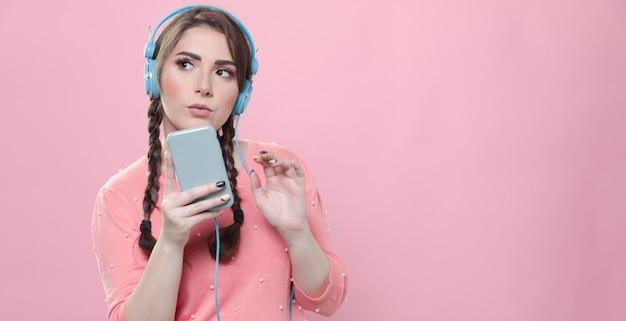 Вид спереди женщины, держащей телефон и слушающей музыку