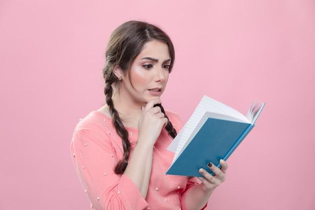 彼女が持っている本の中で読んでいるものにショックを受けた女性の側面図