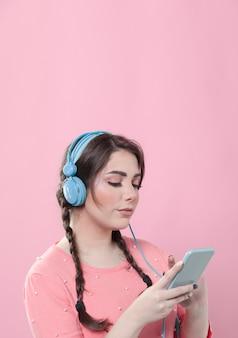ヘッドフォンを着用しながらスマートフォンを見ている女性の側面図
