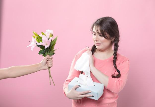 Плачущая женщина отвергает букет лилии, держа салфетки
