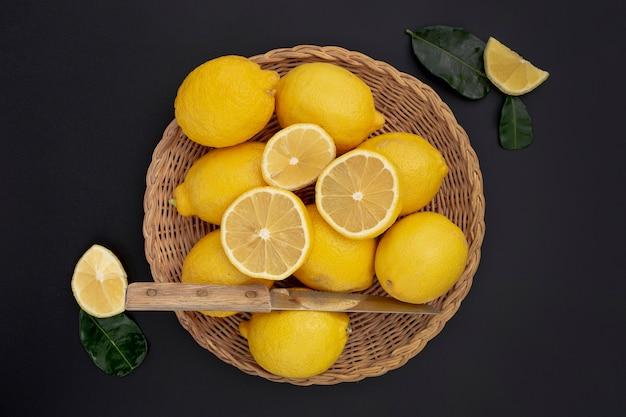 Плоская ложка лимонов в корзине с ножом и листьями