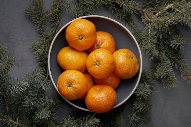 Вид сверху тарелки с мандаринами и сосной