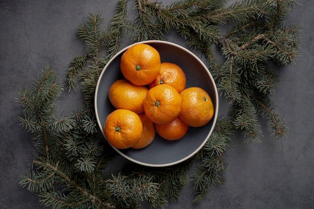 Плоская укладка мандаринов на тарелку с сосной