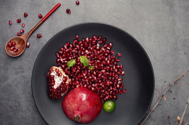 Тарелка с зернами граната и ложкой