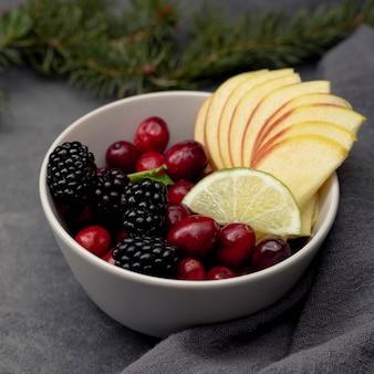 Высокий угол ломтики клюквы и яблок в миске