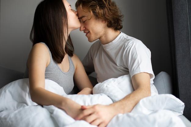 女性が手をつないで男の額にキス