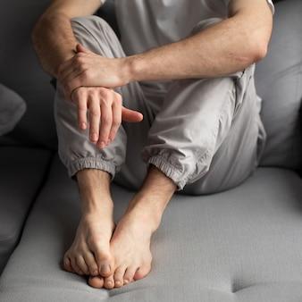 Высокий угол человека, позируя сидя на диване