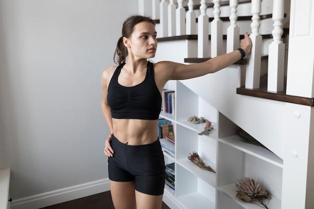 Женщина в спортивной одежде позирует рядом с лестницей