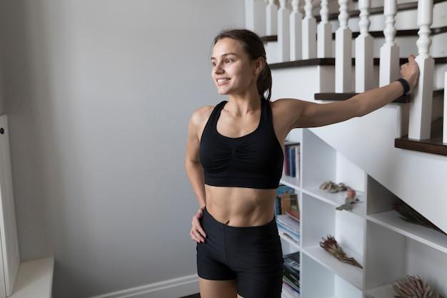 Счастливая спортивная женщина позирует рядом с лестницей