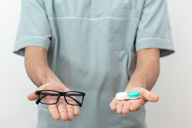 Вид спереди глазного специалиста, держащего очки и контактные линзы
