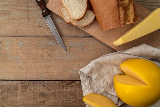 Вид сверху вкусный сыр с хлебом и ножом