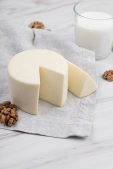 Крупным планом вкусный сыр с грецкими орехами и стакан молока