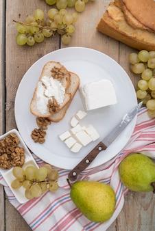 Вид сверху вкусного сыра на ломтик хлеба с виноградом и грушей