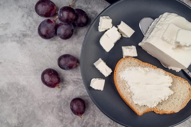 Вид сверху ломтик хлеба с сыром и виноградом
