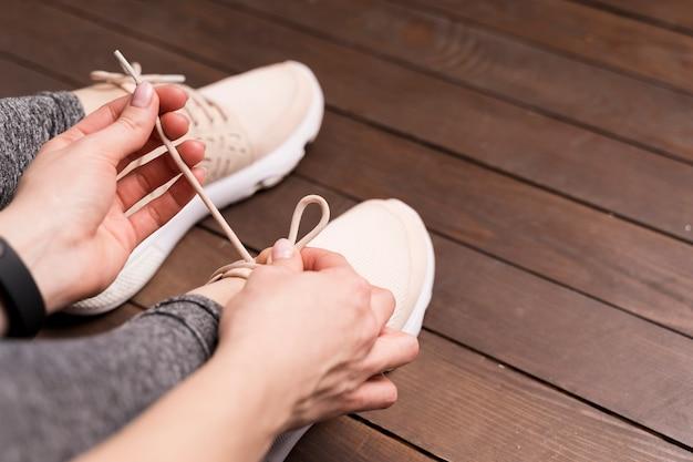 Крупным планом женщина, связывая ее шнурки в тренажерном зале