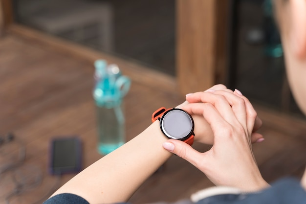 Женщина конца-вверх проверяя ее часы перед тренировкой