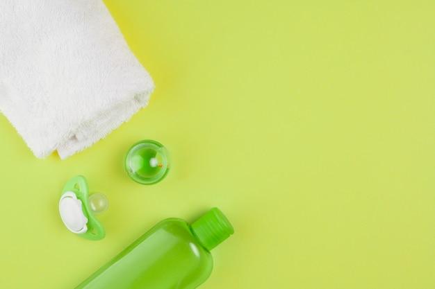 Вид сверху бутылки масла с полотенцем и соской для детского душа