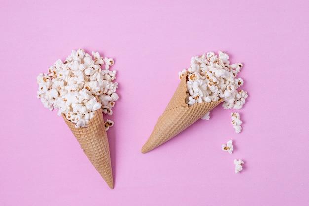 ポップコーンの抽象的な概念で満たされたアイスクリームコーン
