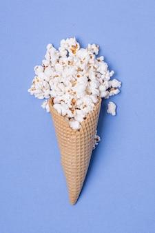 アイスクリームコーンに塩味のポップコーンのシンプルなコンセプト