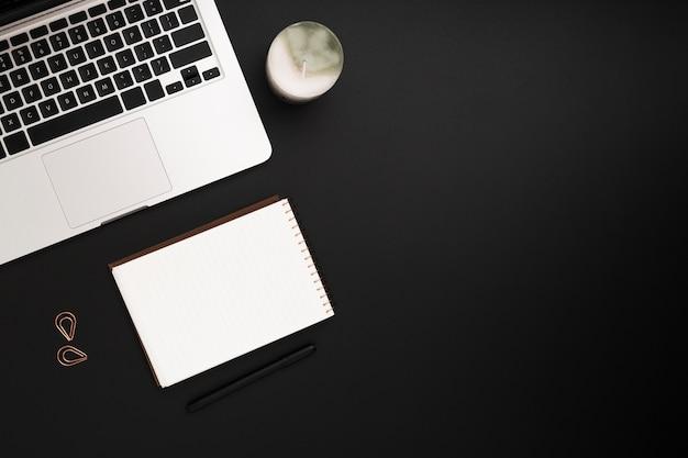 Вид сверху рабочей области с листом бумаги и ноутбуком