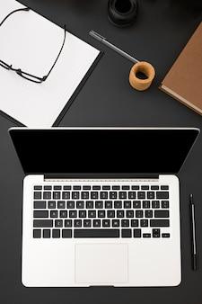 Вид сверху рабочего стола с ноутбуком и очками