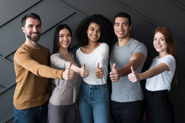 Вид спереди группа молодых людей с большими пальцами руки вверх