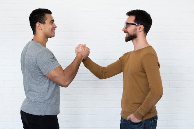 Позитивные взрослые мужчины, держась за руки
