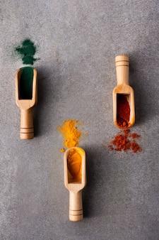カラフルなスパイスとクローズアップの木製スプーン