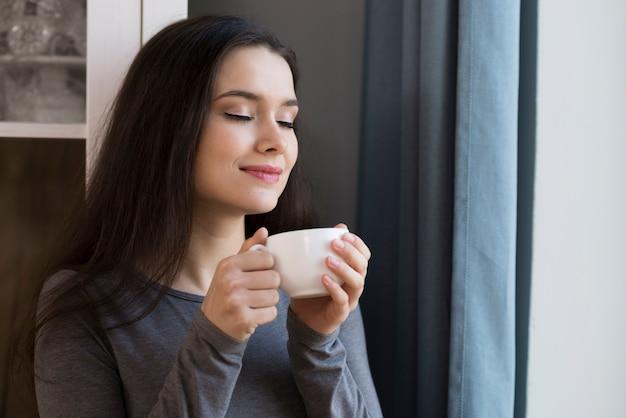 一杯のコーヒーを楽しんでいるクローズアップの美しい若い女性
