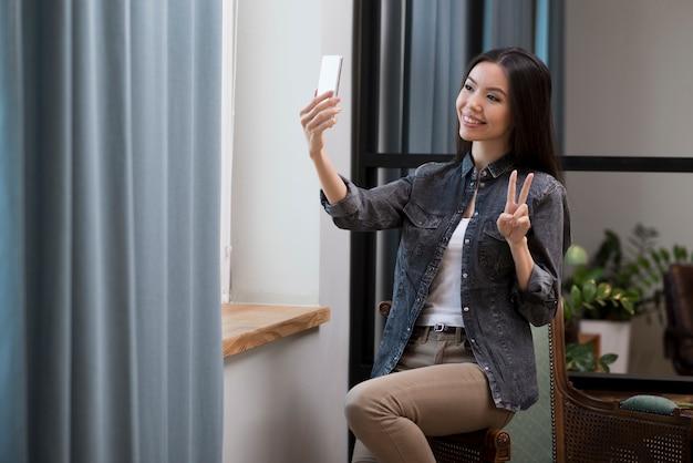 肯定的な若い女性が写真を撮る