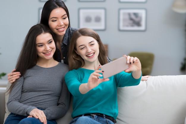 Позитивные молодые женщины, принимая селфи вместе