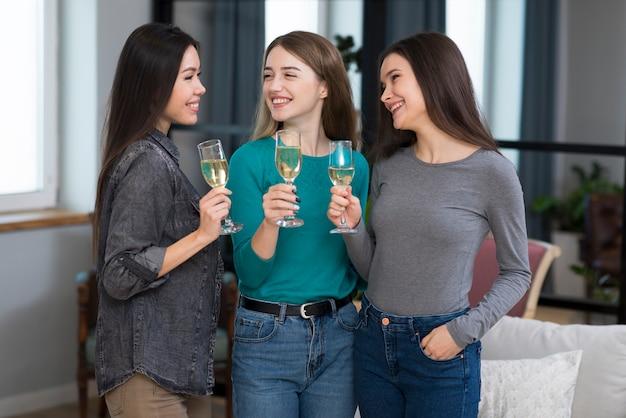 Позитивные молодые женщины празднуют с шампанским