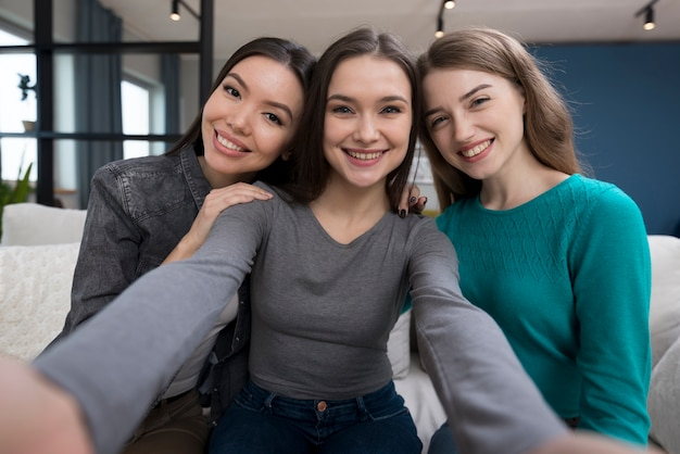 ポジティブな若い女性が一緒に写真を撮る