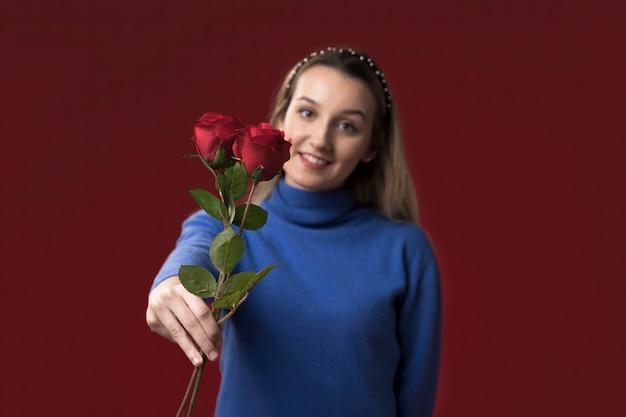 花を保持しているクローズアップの女性