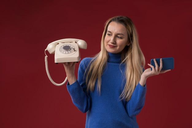 Женщина держит старый и новый телефон