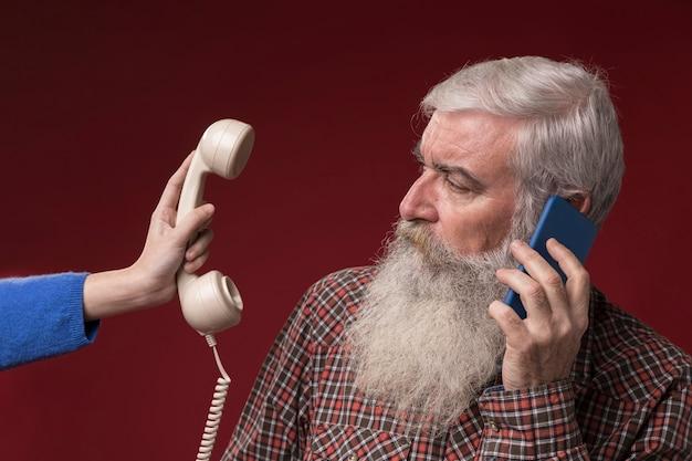 新旧の電話を持つ老人