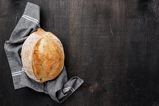 コピースペースの木製の背景が付いている布に丸いパン