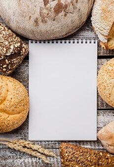 Пустой блокнот, окруженный расположением хлеба