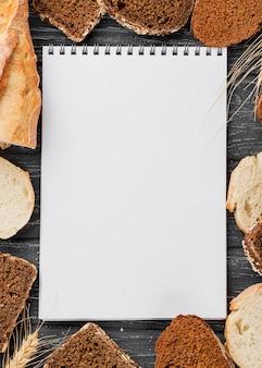 Пустой белый блокнот в окружении ломтиков хлеба