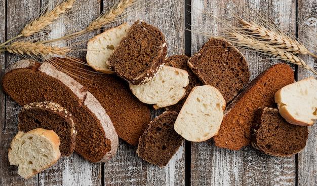 Различные ломтики хлеба на деревянной доске фоне плоской планировки