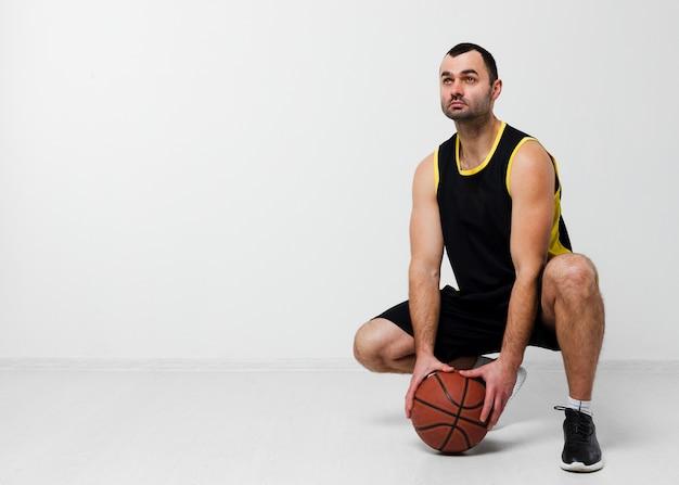 コピースペースでバスケットボールを保持している男の正面図