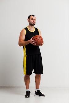ボールでポーズをとってリラックスしたバスケットボール選手の正面図