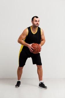 バスケットボールを保持しているオスのプレーヤーの正面図