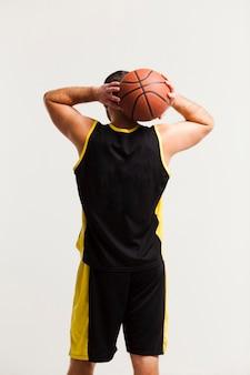 頭の近くにバスケットボールを保持しているオスのプレーヤーの背面図