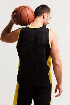 肩にボールを保持しているバスケットボール選手の背面図