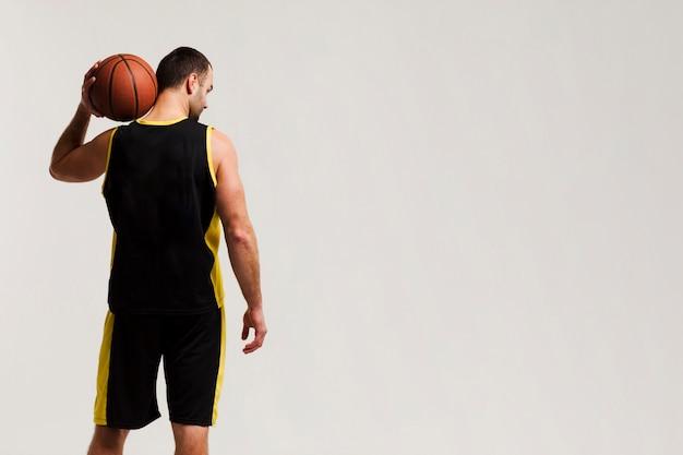 コピースペースと肩にボールを保持しているバスケットボール選手の背面図